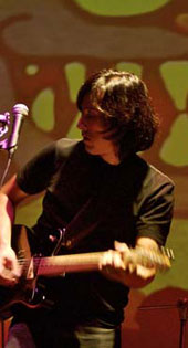 Will Tang playing guitar on stage
